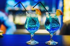 Deux verres de cocktail bleu Martini avec l'orange et les glaçons et les pailles sur la barre Photographie stock