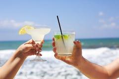 Deux verres de cocktail dans des mains de l'homme et de femme Photos stock