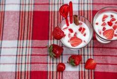 Deux verres de cocktail de lait, fraises fraîches rouges avec du plastique Photos stock