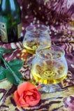 Deux verres de cognac avec des roses rouges et une bouteille sur un fond coloré Images stock