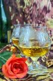Deux verres de cognac avec des roses rouges et une bouteille sur un fond coloré Image stock