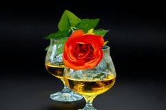 Deux verres de cognac avec la rose de rouge Photographie stock libre de droits