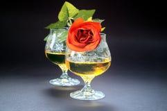 Deux verres de cognac avec la rose de rouge Photos stock