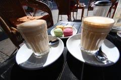 Deux verres de crème de latte avec le dessert de Français de macaron Photographie stock libre de droits