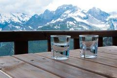 Deux verres de grappa sur la table en bois de la terrasse d'hôtel de montagne photographie stock libre de droits