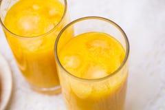Deux verres de jus d'orange avec de la glace sur le blanc Photos stock