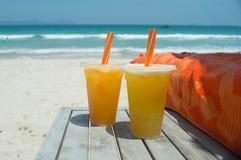 Deux verres de jus d'orange frais sur la plage sablonneuse blanche devant la mer Photo stock