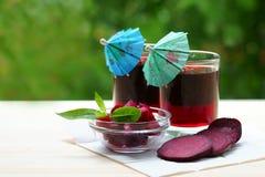 Deux verres de jus de betterave avec des parapluies Image stock