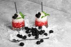 Deux verres de jus rouge et de glace blanche, cuillère argentée, pailles à boire, menthe, mûres sur un fond gris-clair Image stock