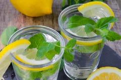 Deux verres de l'eau, de citron et de menthe Images stock