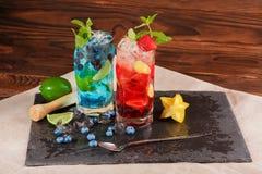 Deux verres de mojitos sur un fond en bois Cocktails avec le carambolier, la menthe et la glace Mojito bleu doux Mojito froid de  photo stock