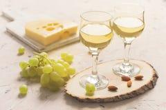 Deux verres de vin blanc avec des raisins, le fromage et des écrous Photographie stock