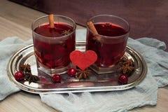 Deux verres de vin chaud avec l'anis de cerises, de cannelle et d'étoile pour des amants Photo stock