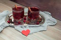 Deux verres de vin chaud avec l'anis de cerises, de cannelle et d'étoile pour des amants Images stock