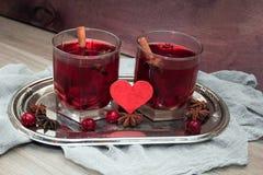 Deux verres de vin chaud avec l'anis de cerises, de cannelle et d'étoile pour des amants Photos stock
