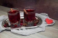 Deux verres de vin chaud avec l'anis de cerises, de cannelle et d'étoile pour des amants Photo libre de droits