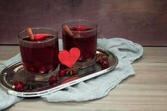 Deux verres de vin chaud avec l'anis de cerises, de cannelle et d'étoile pour des amants Photographie stock libre de droits