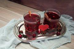 Deux verres de vin chaud avec l'anis de cerises, de cannelle et d'étoile pour des amants Image libre de droits