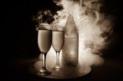 deux verres de vin et de bouteille au-dessus de fond brumeux modifié la tonalité Image de deux verres de vin avec le champagne le Images stock