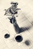 Deux verres de vin et d'une rose de rouge dans un vase Image stock