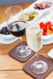 Deux verres de vin mousseux et de vin rouge sur une table en bois Photographie stock