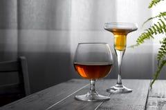 Deux verres de vin placés sur une table en bois sur le fond d'une fenêtre avec un rideau blanc Lumière naturelle d'a photographie stock libre de droits