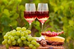 Deux verres de vin rosé avec de la viande, le raisin, le pain et le fromage sur t Image libre de droits