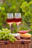 Deux verres de vin rosé avec de la viande, le raisin, le pain et le fromage sur t Images libres de droits