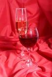 Deux verres de vin rouge et blanc sur le fond rouge Photographie stock
