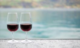 Deux verres de vin rouge sur la barre au-dessus de la tache floue verdissent le fond de lac Photo libre de droits
