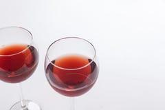 Deux verres de vin rouge sur le fond blanc Photographie stock
