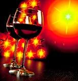 Deux verres de vin rouge sur le fond d'or d'arbre de lumières Images stock