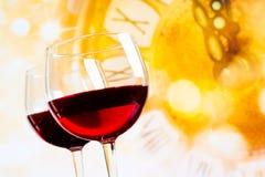 Deux verres de vin rouge sur le fond d'or d'horloge Images stock