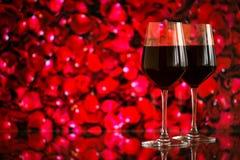 Deux verres de vin rouge sur le fond de bokeh avec des étincelles et des roses Profondeur de champ très Image stock