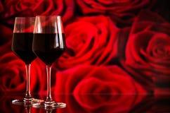 Deux verres de vin rouge sur le fond de bokeh avec des étincelles et des roses Profondeur de champ très Image libre de droits
