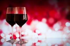 Deux verres de vin rouge sur le fond de bokeh avec des étincelles et des roses Profondeur de champ très Photographie stock