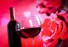 Deux verres de vin rouge sur le fond de roses rouges de tache floue Photo stock