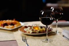 Deux verres de vin rouge sur le fond des plats dans le r Photos libres de droits