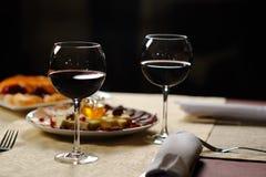 Deux verres de vin rouge sur le fond des plats dans le r Photo stock