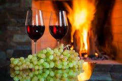 Deux verres de vin rouge sur le fond du feu Photographie stock libre de droits