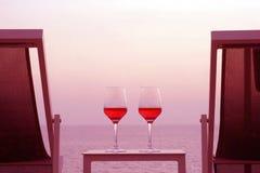 Deux verres de vin rouge sur le fond de la mer Images libres de droits