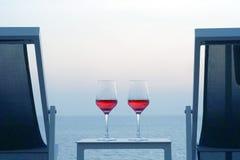 Deux verres de vin rouge sur le fond de la mer Image libre de droits