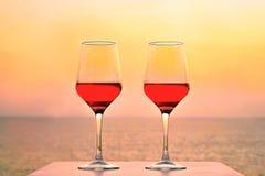 Deux verres de vin rouge sur le fond de la mer Image stock