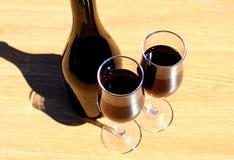 Deux verres de vin se tiennent sur une table sous la lumière du soleil directe image stock