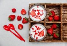 Deux verres de yaourt, fraises fraîches rouges dans la boîte de rotin avec les cuillères en plastique sur le livre blanc Sain org Photographie stock