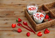 Deux verres de yaourt, fraises fraîches rouges dans la boîte de rotin avec les cuillères en plastique sur le Tableau en bois Peti Images stock