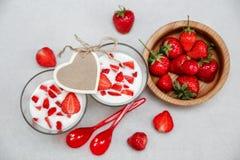 Deux verres de yaourt, les fraises fraîches rouges sont dans le plat en bois avec les cuillères en plastique, carte de coeur de s Image libre de droits