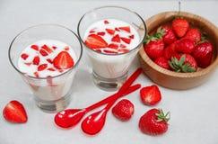 Deux verres de yaourt, les fraises fraîches rouges sont dans le plat en bois avec les cuillères en plastique, sur le livre blanc  Photos libres de droits