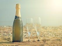 Deux verres et une bouteille de champagne sur une plage sablonneuse un jour chaud d'été Photo stock