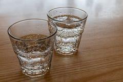 Deux verres fraîchement versés de l'eau de scintillement d'isolement sur le bois Photos libres de droits